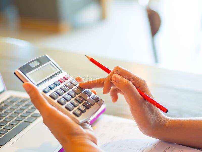 特写镜头使用一个计算器的女商人手有红色铅笔的在咖啡馆办公室 免版税库存图片