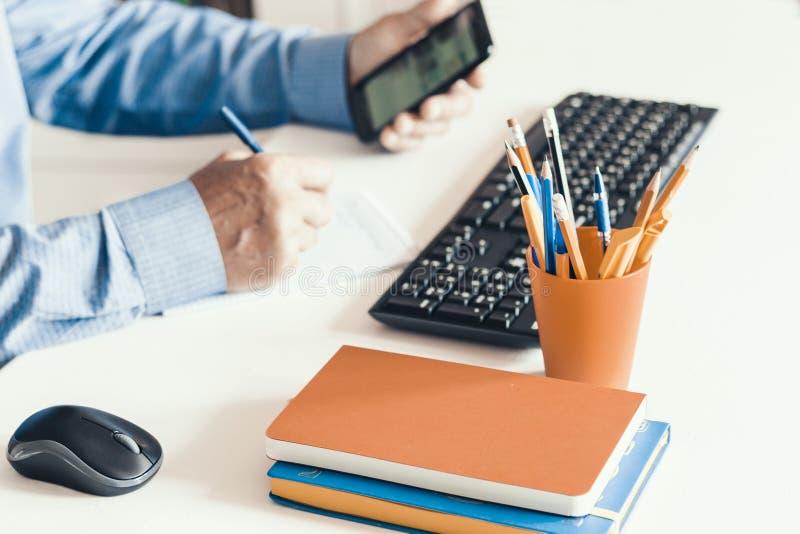 特写镜头使用智能手机的手人和键入在白色桌,企业概念上的键盘计算机上 图库摄影