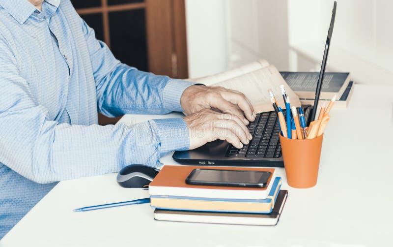 特写镜头使用老鼠的手人和键入在白色桌,企业概念上的膝上型计算机 库存图片