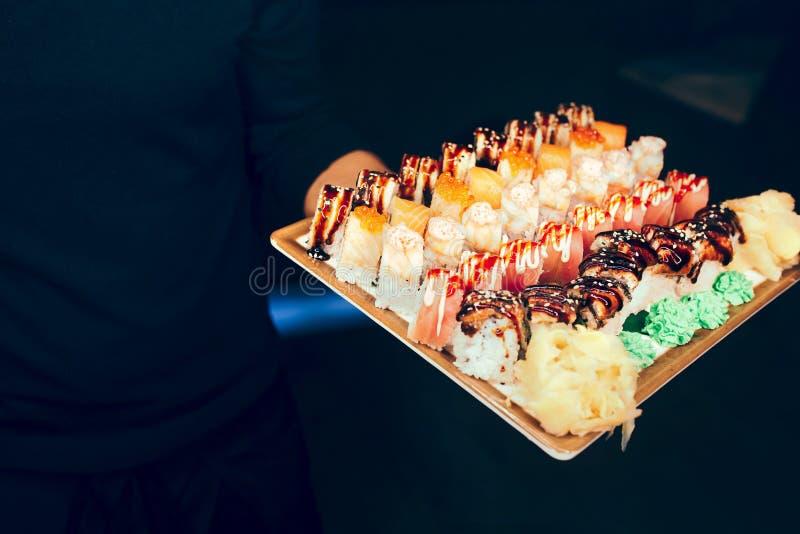 特写镜头侍者藏品套寿司红色贪婪龙,金枪鱼北海道加利福尼亚Tobico费城卷自助餐在用餐稀土的夜 库存图片