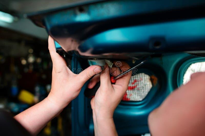 特写镜头修理在车库的一辆残破的蓝色汽车用人工machanic 图库摄影