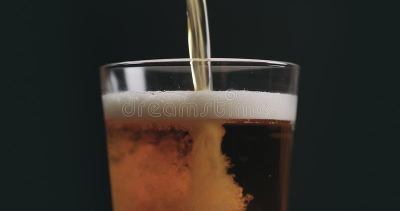 特写镜头倒在品脱玻璃的清淡的强麦酒啤酒在黑背景 免版税库存图片