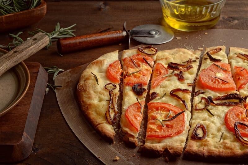 特写镜头切了Focaccia和焦糖的葱蕃茄和新鲜的罗斯玛丽 免版税库存照片