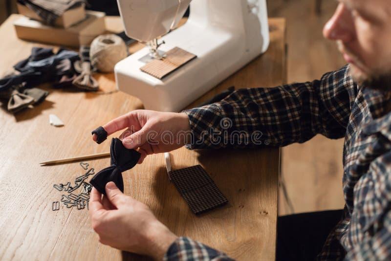 特写镜头创造蝴蝶领带的形状由羊毛制成 悦目年轻人工作作为裁缝和使用a 库存照片