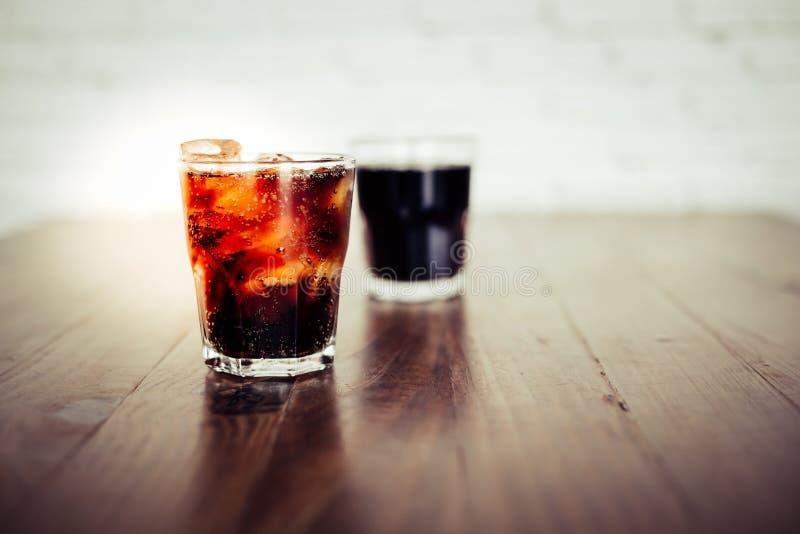 特写镜头可乐或汽水 在一块玻璃的冷的可乐与在木桌上的冰块 可乐口味是很可口的,当您 库存照片