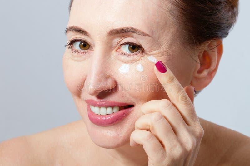 特写镜头和中部宏指令画象变老了有奶油的妇女在白色背景的面孔 皱痕和更年期 胶原 库存照片