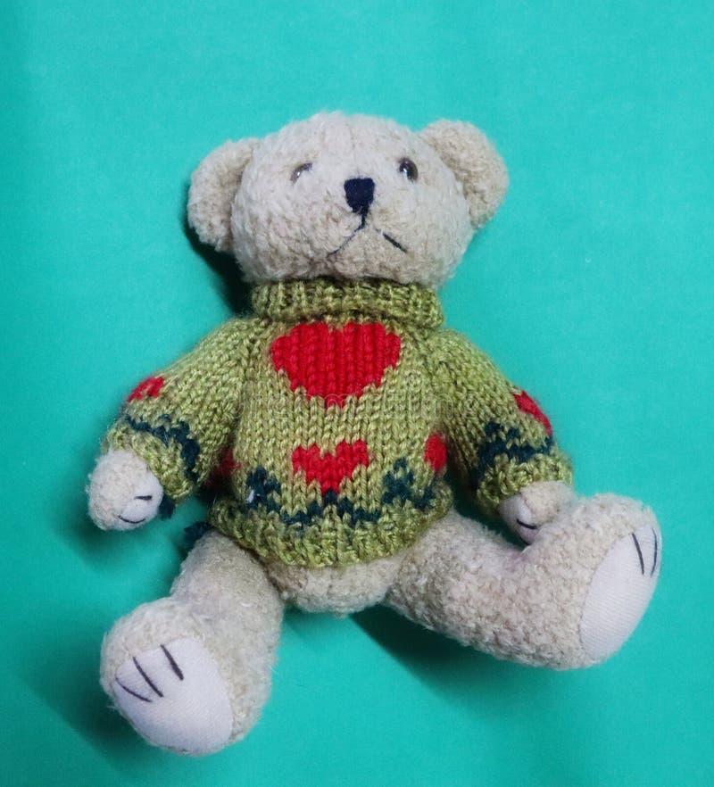 特写镜头图片,顶视图,佩带冬天外套绿色背景的逗人喜爱的玩具熊 免版税库存图片
