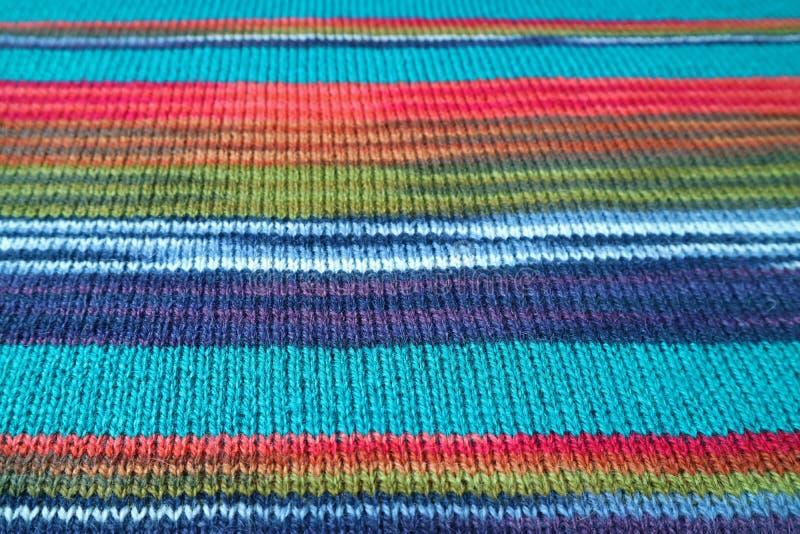 特写镜头土耳其玉色纹理与五颜六色的镶边羊魄的编织了背景的羊毛织品 免版税库存照片