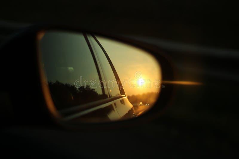特写镜头在一个汽车的镜子反映的被射击日落有被弄脏的黑暗的背景 免版税图库摄影