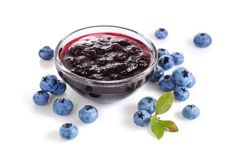 特写镜头在玻璃碗的视图果酱用新鲜的成熟蓝莓和叶子 免版税库存照片