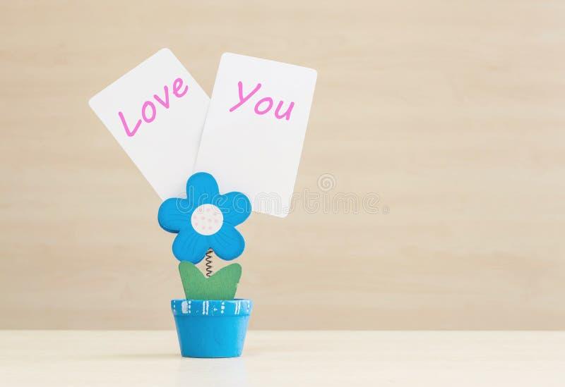 特写镜头在蓝色花形状形状的钳位照片在充满您在被弄脏的木书桌和墙壁后面的白皮书措辞的爱的花盆 库存图片