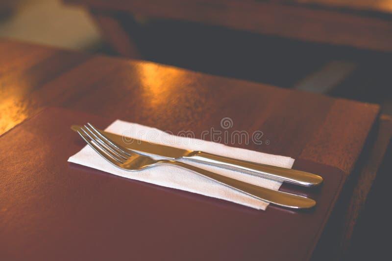特写镜头在餐巾的叉子和刀子谎言在桌上 免版税库存图片