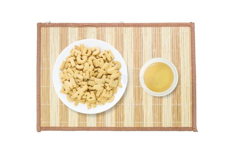 特写镜头堆在英语字母表的棕色饼干在白色盘和在白色陶瓷杯子的棕色茶在白色b隔绝的木席子 库存照片