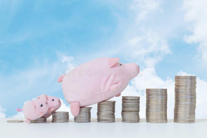 特写镜头堆硬币开始从低落到与猪玩偶和三小的猪步行的上流在硬币上面与木书桌和蓝色 免版税库存图片