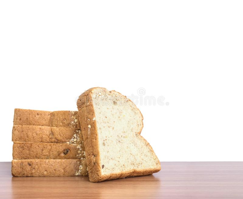 特写镜头堆麦子面包在白色背景隔绝的棕色木书桌上的早餐 库存照片