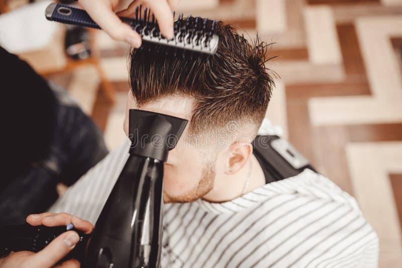 特写镜头大师理发师对发型和称呼与干毛发做人 概念理发店 库存照片
