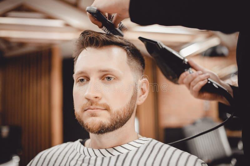 特写镜头大师理发师对发型和称呼与干毛发做人 概念理发店 免版税库存图片