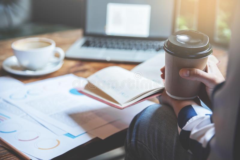 特写镜头女商人递拿着笔记本和咖啡 免版税库存图片