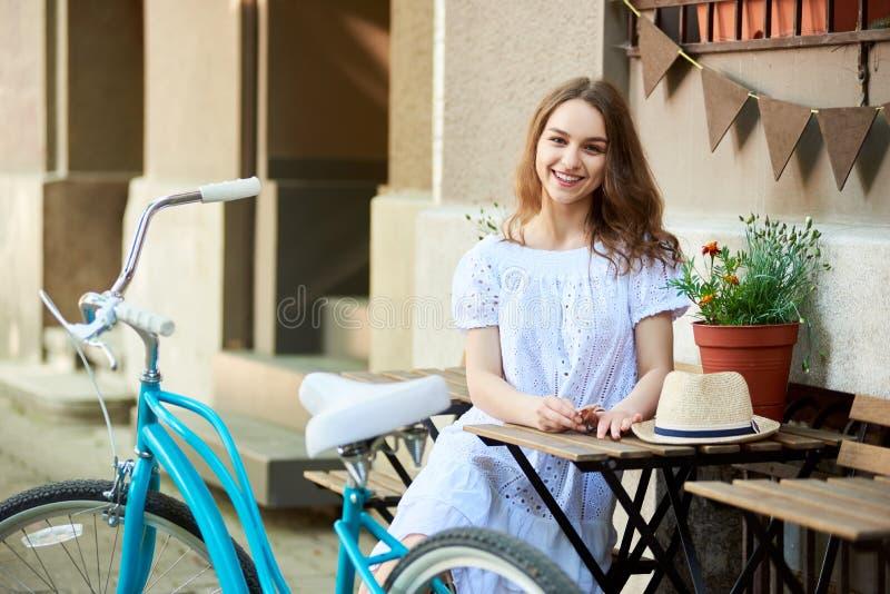 特写镜头女孩坐大阳台街道咖啡馆在减速火箭的自行车附近 库存图片