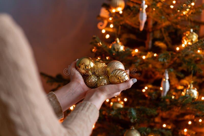 特写镜头妇女在金黄圣诞树玩具的手上举行 在房子内部的寒假 金黄和白色 库存图片