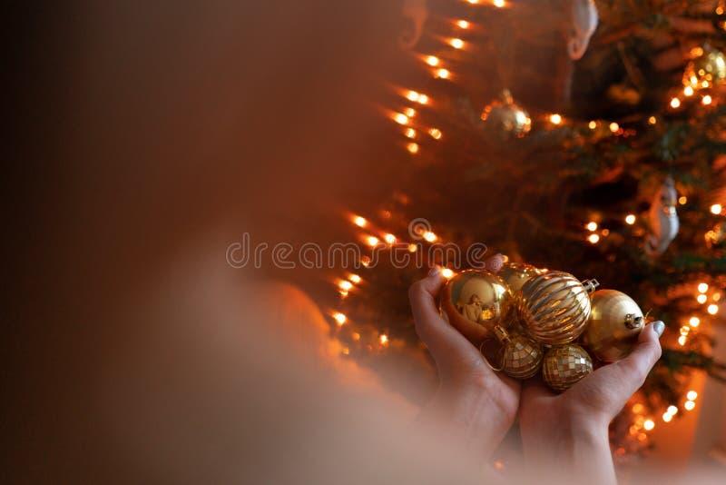 特写镜头妇女在金黄圣诞树玩具的手上举行 在房子内部的寒假 金黄和白色 免版税库存图片