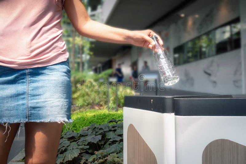 特写镜头妇女手是投掷塑料一个瓶水入垃圾在百货店回收,除地球概念外 免版税库存图片