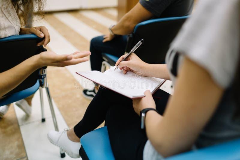 特写镜头学生写和谈话在教室背景 新的研究材料概念 库存照片