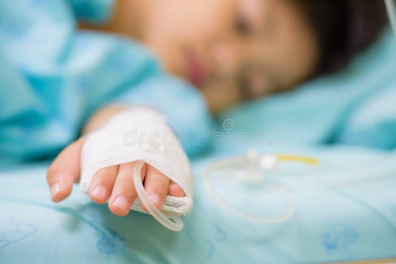 特写镜头孩子手在一张床上睡觉在医院 免版税库存图片