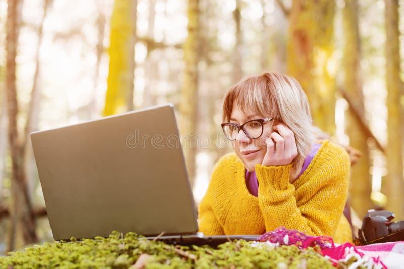 特写镜头定了调子一张自由职业者女孩画象的图象在周道地看膝上型计算机的一件黄色毛线衣和玻璃的 库存照片