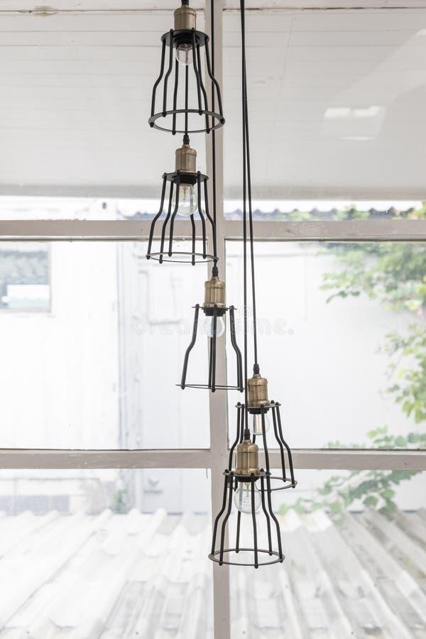 特写镜头小组在透明窗口背景的天花板黑色金属垂悬的枝形吊灯灯 图库摄影