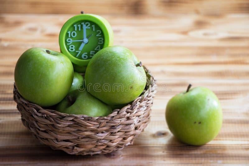 特写镜头小组绿色苹果和时钟在被编织的篮子 免版税库存图片