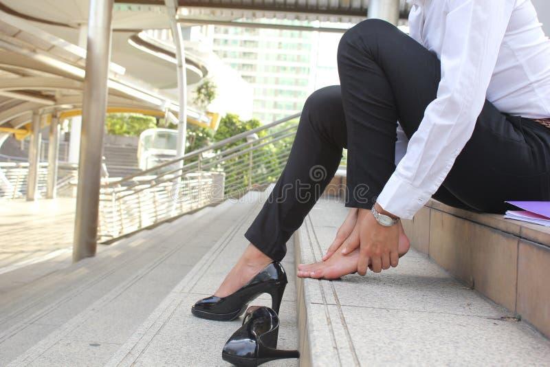 特写镜头年轻女人感觉的痛苦在她的在台阶的脚,有脚腕痛苦,健康概念 图库摄影