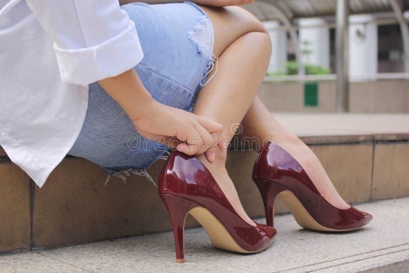 特写镜头年轻女人感觉的痛苦在她的在台阶的脚,有脚腕痛苦,健康概念 库存照片