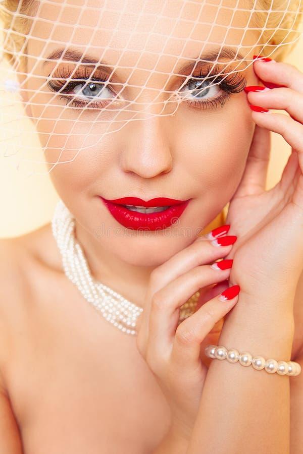 特写镜头年轻女人秀丽画象有红色嘴唇、长的假睫毛和白色减速火箭的帽子的有滤网的 库存照片