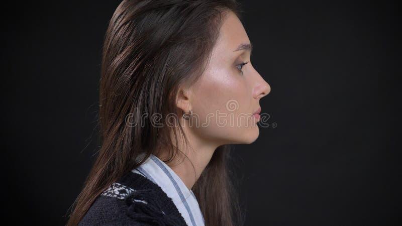 特写镜头年轻逗人喜爱的白种人女性面孔侧视图画象与今后看与隔绝的深色的头发的 免版税库存照片