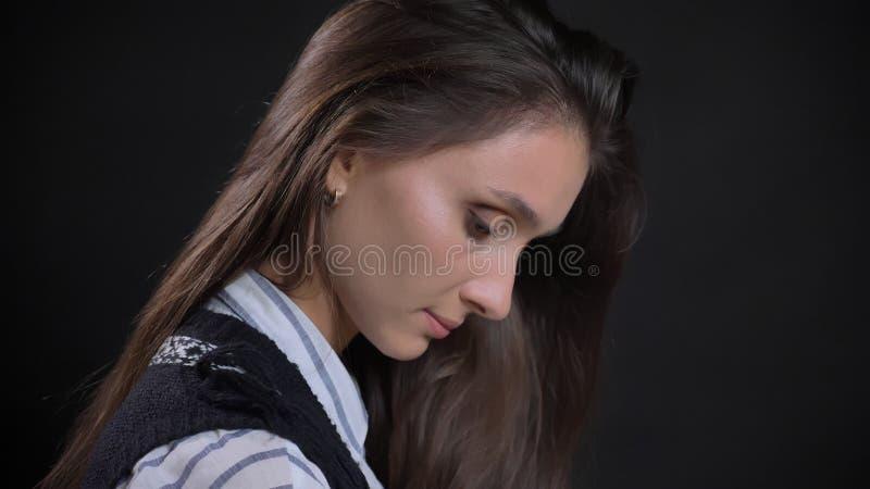 特写镜头年轻逗人喜爱的白种人女性面孔侧视图画象与看下来有被隔绝的背景的深色的头发的 免版税图库摄影