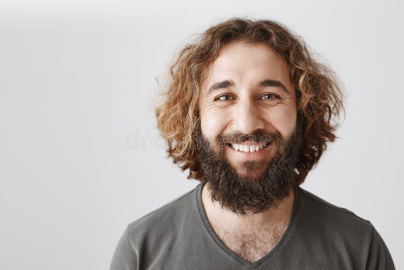 特写镜头广泛地微笑射击了有卷发的英俊的快乐的阿拉伯人和胡子,当谈话与他的工友时 免版税库存图片