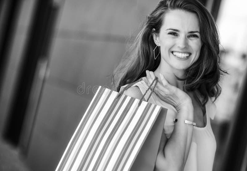 特写镜头微笑,拿着stripey袋子的棕色毛发的妇女 免版税库存图片