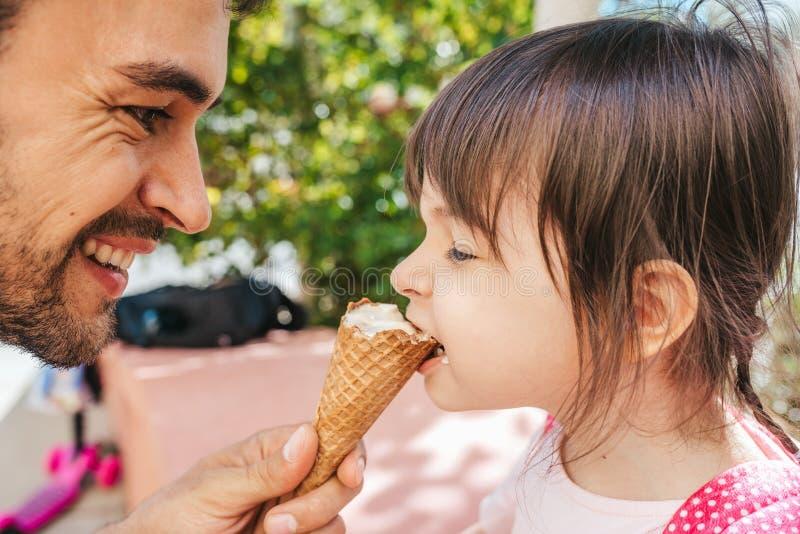 特写镜头愉快的逗人喜爱的女孩侧视图画象有英俊的爸爸品尝和吃冰淇凌的户外 乐趣女孩孩子和 免版税库存照片
