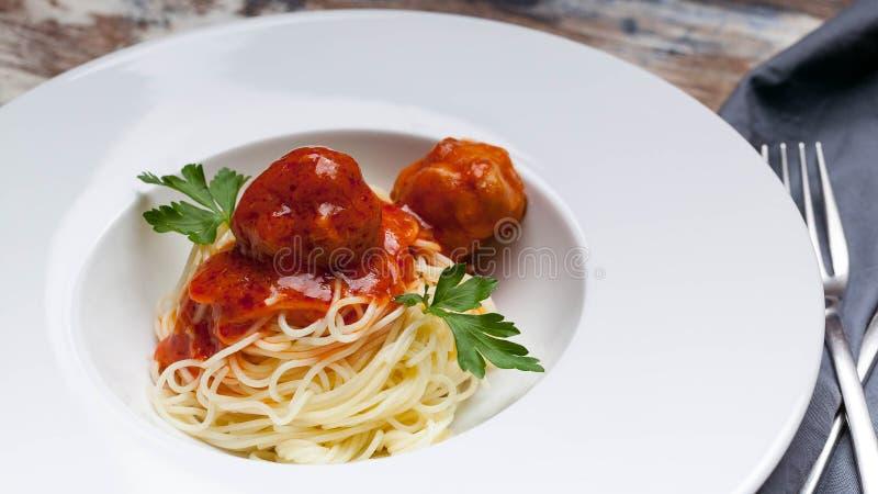 特写镜头意粉和丸子在西红柿酱在一块白色板材 免版税图库摄影