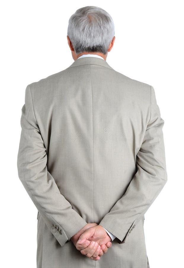 特写镜头成熟,从后面看见的商人用在他的后面后被扣紧的他的手 图库摄影
