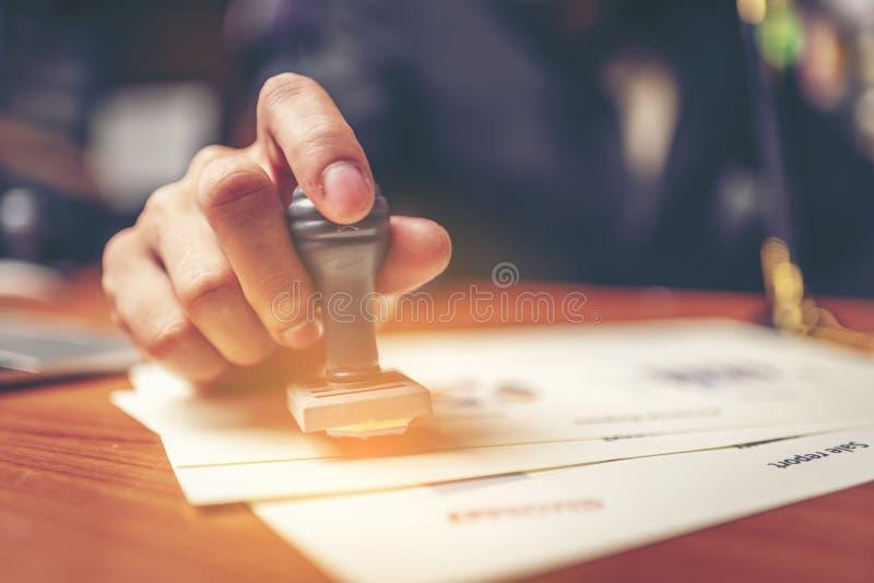 特写镜头手盖印签署的认同的商人  库存图片