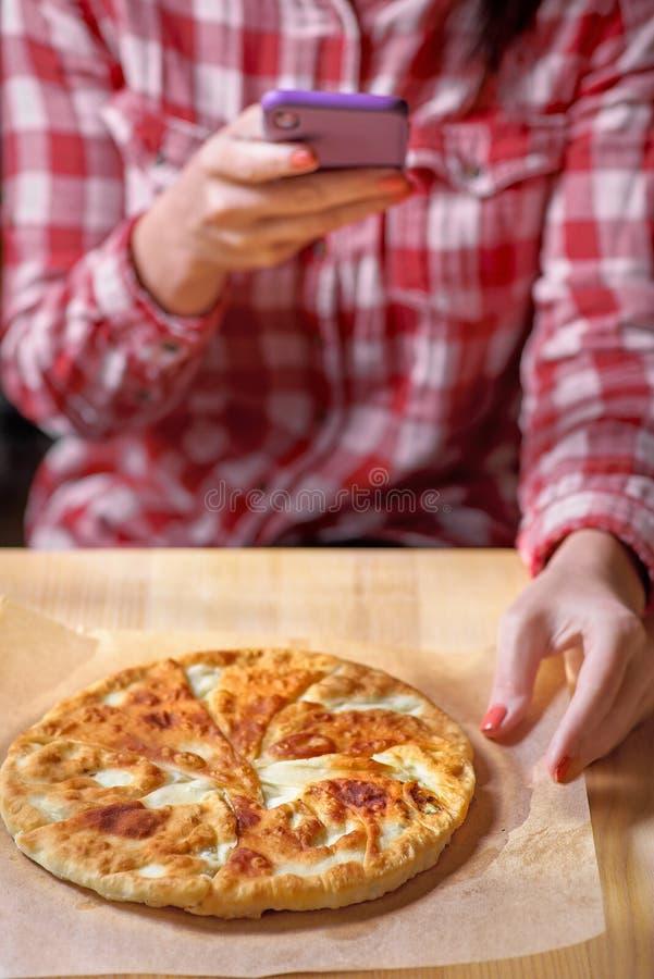 特写镜头手藏品电话射击食物照片一张桌在一红色格子衬衫的一家餐馆 r 免版税库存照片