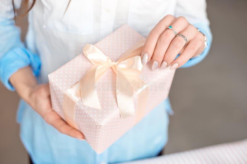 特写镜头拿着一件小礼物的被射击女性手包裹与桃红色丝带 小礼物在室内妇女的手上 免版税库存照片