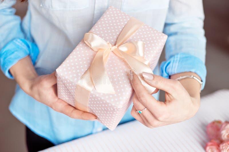特写镜头拿着一件小礼物的被射击女性手包裹与桃红色丝带 小礼物在室内妇女的手上 库存图片
