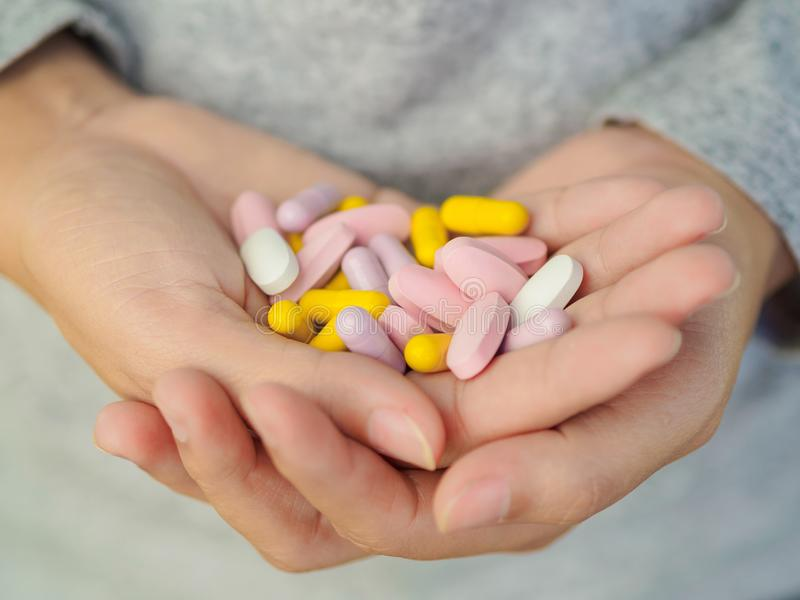 特写镜头拿着很多不同的药片的妇女手 免版税库存照片