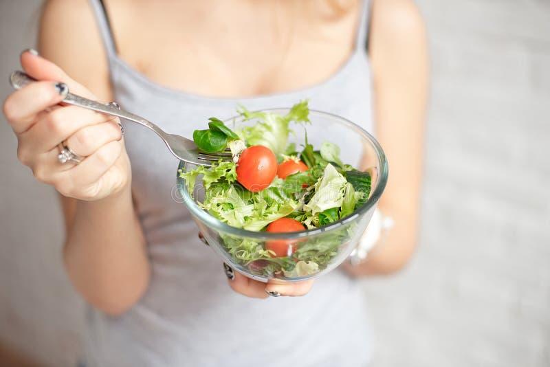 特写镜头拿着碗新鲜蔬菜沙拉的背面图妇女拿着叉子手中 免版税库存图片