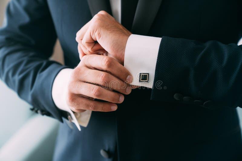 特写镜头新郎手投入链扣 典雅的绅士clothers,白色衬衫 免版税库存图片