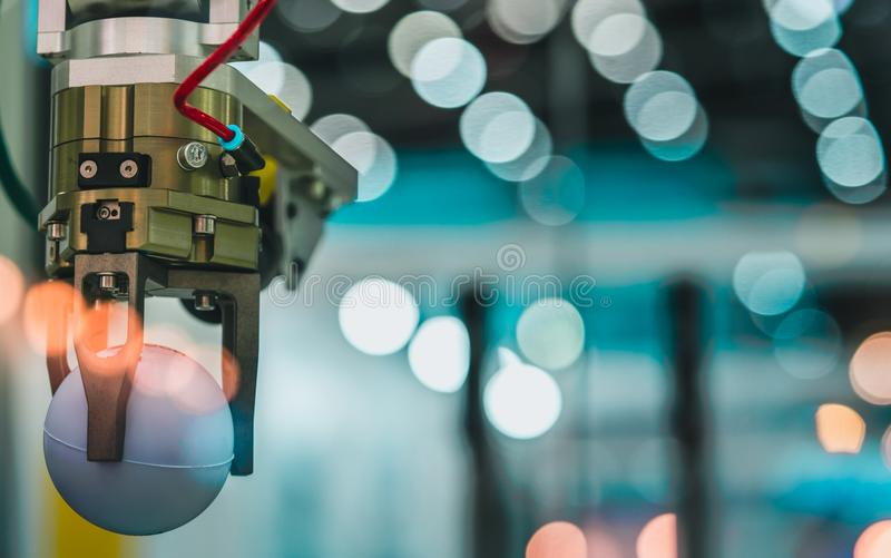 特写镜头机器人拾起在bokeh的手机器白色球弄脏了背景 使用巧妙的机器人在制造工业 机器人 免版税库存图片