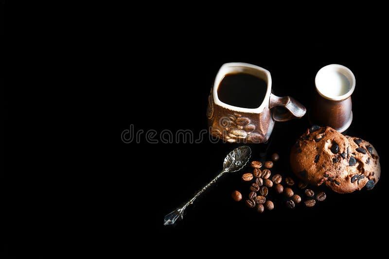 特写镜头杯子浓咖啡咖啡、牛奶和匙子葡萄酒,圆的嘎吱咬嚼的巧克力曲奇饼用在黑背景的咖啡豆, 库存照片
